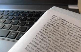Imatge d'un diari amb informació científica i un ordinador